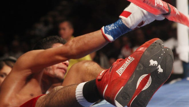 Angel Osuna grabs the rope as he gets back into the ring after being knocked out of the ring by Hugo Centeno.