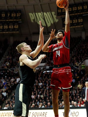 Louisville forward Anas Mahmoud takes a shot against Purdue center Isaac Haas during the second half at Mackey Arena.  Sports