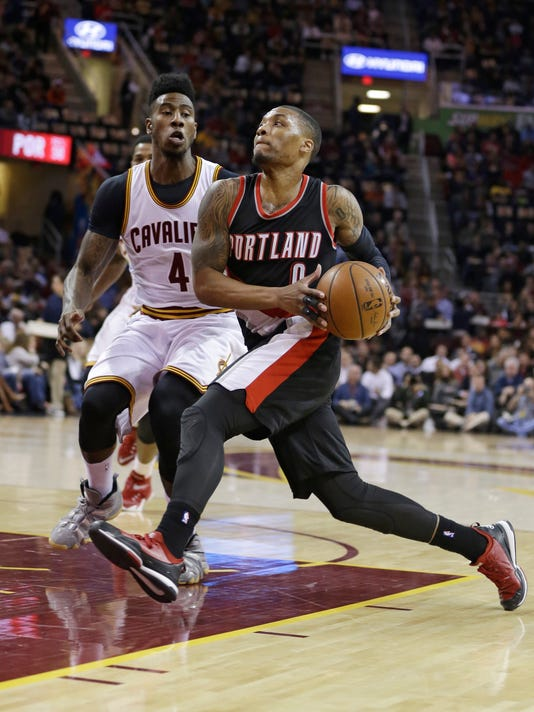 Portland Trail Blazers' Damian Lillard (0) drives past Cleveland Cavaliers'  Iman Shumpert (4) during the first quarter of an NBA basketball game Wednesday, Jan. 28, 2015, in Cleveland. (AP Photo/Tony Dejak)