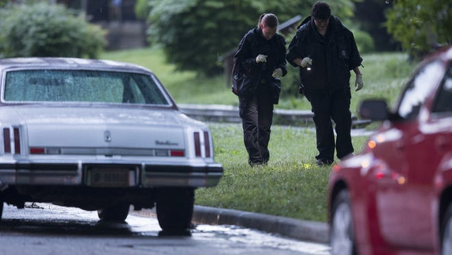 Indianapolis Metropolitan Police officers search for evidence from a shooting early Wednesday, June 11, 2014,on Brookside Parkway North Drive on Indianapolis' Eastside.