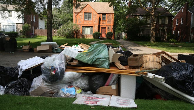 Some of the garbage piling up in front of Percy Davis' home in Detroit on Tuesday. After the heavy rain fell on metro Detroit last week, lots of basements were flooded, and homeowners were looking for help.