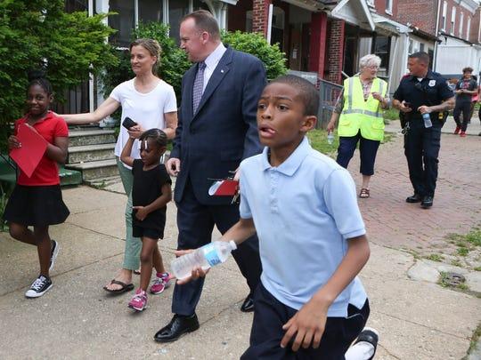 Wilmington Police Chief Robert Tracy (center) and other officers, as well as teachers and students from Lombardy Elementary School, join members of Safe United Neighborhoods in their regularly scheduled neighborhood walkabout on a Friday night.