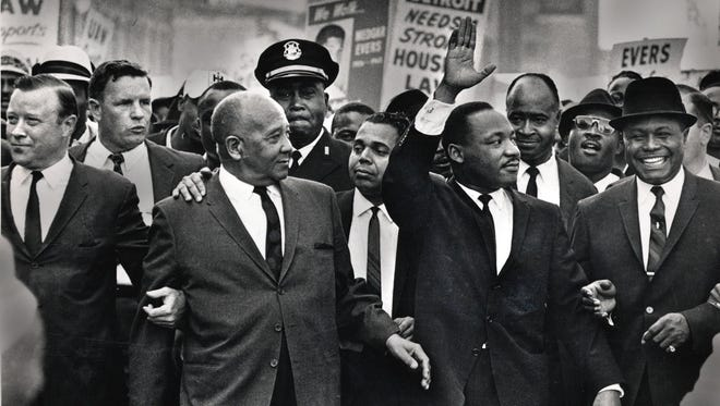 "The Rev. Martin Luther King Jr. waves to onlookers as he leads the 125,000 strong ""Walk to Freedom"" on Woodward Avenue in Detroit  in 1963.  From left to right in the front row are: Walter Reuther, Benjamin McFall, Commander George Harge (cop with cap), Dr. King, and the Rev. C.L. Franklin."