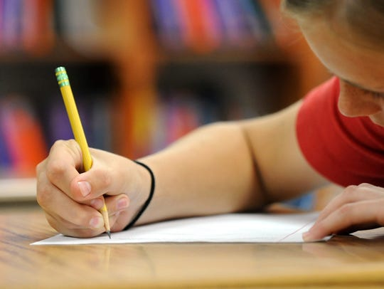 A student is shown writing in this file photo.