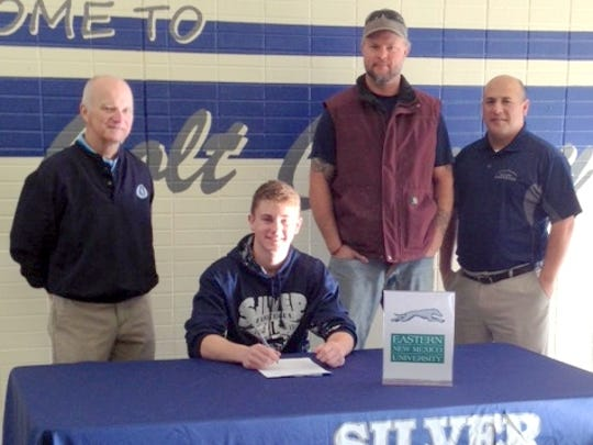 Silver High's Jeremiah Burke signs his letter of intent to play football at Eastern New Mexico University. His father, ex coach Butch Branson and head coach Raul Diaz are present.