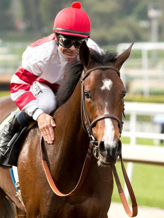 In a photo provided by Benoit Photo, Mike Smith pats Songbird after their win in the Grade III $100,000 Santa Ysabel Stakes horse race Saturday, March 5, 2016, at Santa Anita in Arcadia, Calif. (Benoit Photo via AP)