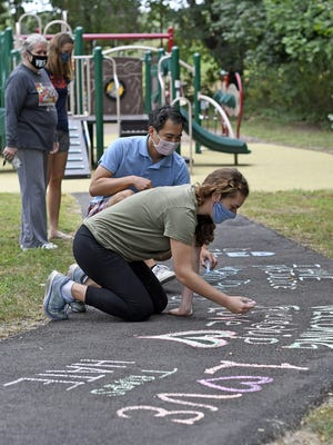 Anna Sangree and Andrew Huang joined residents who created chalk art at the Stoney Brae Playground in Quincy on Saturday afternoon after a racial graffiti was found on the play set.