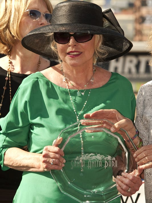 In this photo provided by Benoit Photo, singer/songwriter Michelle Phillips, of The Mamas and The Papas, makes the trophy presentation to Unusual Heatwave's connections after victory in the $100,000 Crystal Water Stakes horse race, Sunday,  June 8, 2014, at Santa Anita Park in Arcadia, Calif. (AP Photo/Benoit Photo)