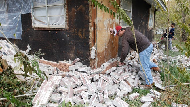 Chad Devereaux examines bricks that fell from three sides of his in-laws' home in Sparks, Okla., in 2011, following two earthquakes that hit the area in less than 24 hours. New research suggests the rise in quake activity in Oklahoma may be tied to deepwater injection wells.