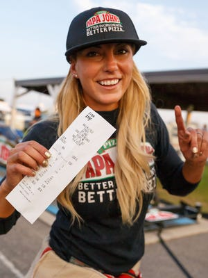 NHRA Top Fuel driver Leah Pritchett celebrates with her time slip after setting a national record time of 3.640 seconds during qualifying for the Lucas Oil Nationals at Brainerd International Raceway.