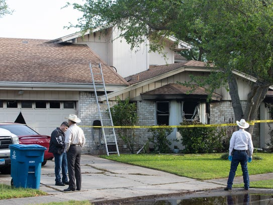 Law enforcement on scene of a homicide and house fire