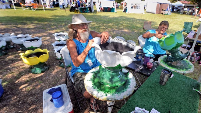 "Artists Bruce and JoAnne Byrd paint their handmade planters made out of recycled tires during the most recent ""New Beginnings Art Show."""