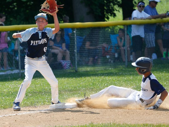 Poughkeepsie Lightning's Steven Ciancio III slides into third base as East Fishkill's Nevin Scapperotti covers the base during Thursday's game at Crown Heights Park in the Town of Poughkeepsie on July 5, 2018.