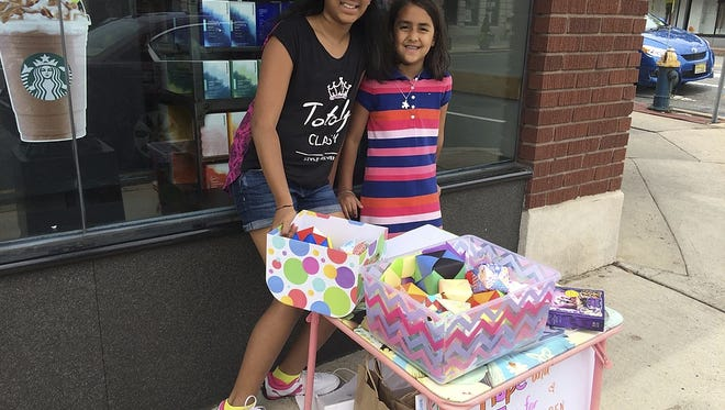 Etasha Donthi and her mother, Sandhya Bohini, staff a table where they sell origami and raise funds to support children in poverty-stricken countries.