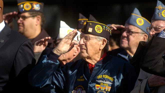 Art Fishman, a World War II Navy veteran, salutes the American flag during Veterans Day ceremonies in Southfield Monday morning.