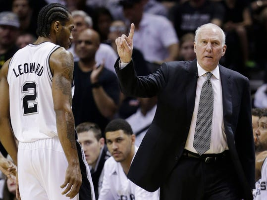 San Antonio Spurs head coach Gregg Popovich signals as forward Kawhi Leonard (2) heads to the sideline against the Miami Heat during the first half in Game 5 of the NBA basketball finals on Sunday, June 15, 2014, in San Antonio. (AP Photo/David J. Phillip)