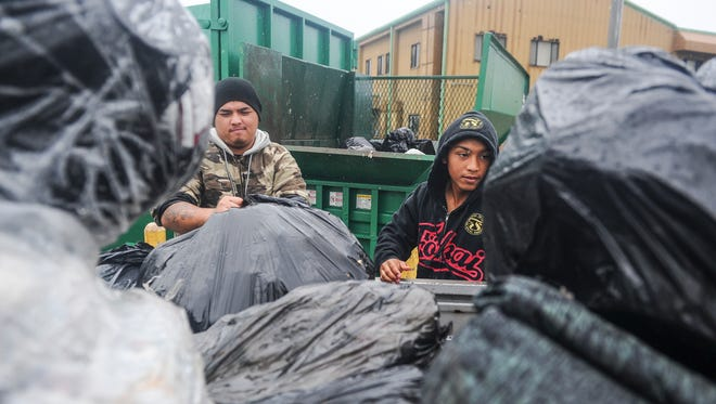 Robby Santos, right, and E.J. Palma unload bags of household trash into a compactor at the Harmon Residential Transfer Station on Thursday, Aug. 4.