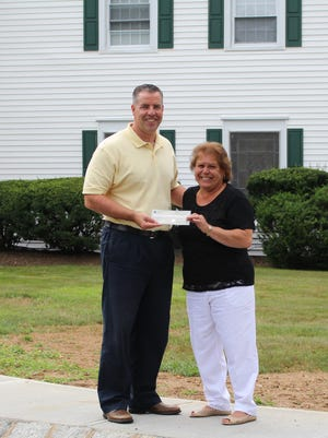 Russell Gartz, Director of External Relations at Collier Youth Services, being presented a $5,000 check from Maria Cetta, Investors Bank Morganville-Marlboro Branch Manager.
