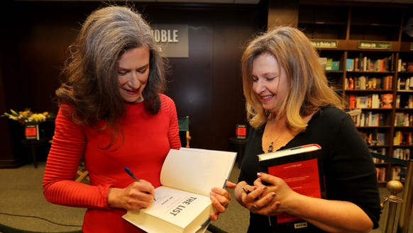 Amy Siskind of Mamaroneck signs a copy of her book