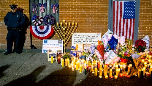 An New York City police officer stands near a growing memorial Sunday, Dec. 21, 2014, near the spot where two New York Police Department officers, sitting inside a patrol car the previous day, were shot by an armed man, killing them both.