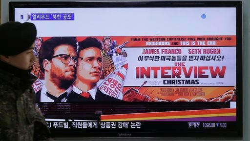 """FILE - In this Dec. 22, 2014 file photo, a South Korean army soldier walks near a TV screen showing an advertisement of Sony Picture's """"The Interview,"""" at the Seoul Railway Station in Seoul, South Korea. Sony's flip-flop decision on releasing """"The Interview"""" shows the studio is working furiously to try to chart the right course through political and public-opinion minefields. It's not yet clear whether this will be enough to repair Sony's image, but the decision will at least give the movie-going public a chance to send North Korea a protest message. (AP Photo/Ahn Young-joon, File)"""