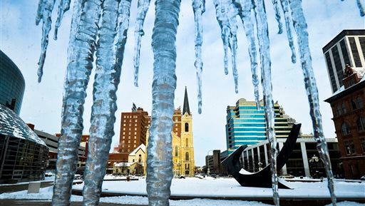 Icicles frame a view of the skyline in Peoria, Ill. Dozens of school districts in Illinois, including Chicago Public Schools, canceled classes on Wednesday, Jan. 7, 2015, because of subzero temperatures.