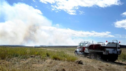 A water truck drives down one of the dirt roads being used to access a fire on what appears to be open land on the plains east of Kersey, Colo., Friday, Sept. 18, 2015. The fire was burning on approximately 3,000 acres Friday. (Joshua Polson/The Greeley Tribune via AP) MANDATORY CREDIT