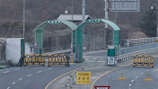 """South Korean Army soldiers move barricades to close the road at the customs, immigration and quarantine office near the border village of Panmunjom in Paju, South Korea, Thursday, Feb. 11, 2016. North Korea on Thursday ordered a military takeover of a factory park that was the last major symbol of cooperation with South Korea, saying Seoul's suspension of operations at the jointly run facility was a """"dangerous declaration of war."""" (AP Photo/Ahn Young-joon)"""