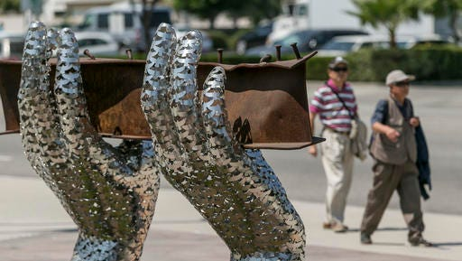 "ADVANCE FOR USE SUNDAY, SEPT. 11, 2016 AND THEREAFTER-In this Friday, Aug. 26, 2016 photo, pedestrians walk by artist Heath Satow's sculpture ""Reflect,"" made with a damaged, rusted I-beam from the collapsed World Trade Center buildings, outside the Rosemead, Calif., city hall plaza. The 9/11 memorial sculpture has 2,976 interlocking birds representing individual victims from the 2001 attacks. (AP Photo/Damian Dovarganes)"