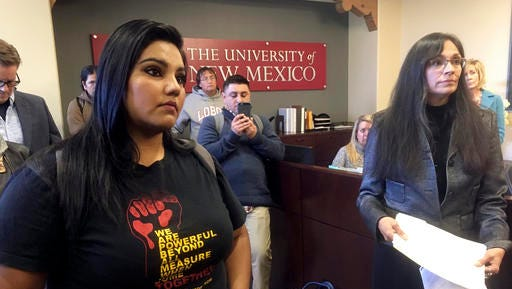 """University of New Mexico student LuzHilda Campos, left, and Chicano studies professor Irene Vasquez, right, present a letter with hundreds of signatures on Friday, Nov. 18, 2016, to school president Bob Frank asking him to declare the campus a """"sanctuary university,"""" in Albuquerque, N.M. A group of professors at the largest university in the nation's most Hispanic state are asking for more protection of immigrant students following the election of Republican Donald Trump."""