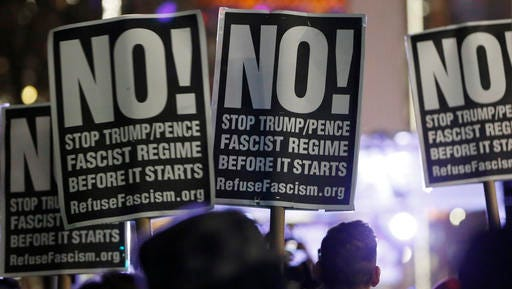 People attending an anti-Trump rally and protest hosted by filmmaker Michael Moore hold signs as they listen to speakers on a stage set up in front of the Trump International Hotel, Thursday, Jan. 19, 2017, in New York. President-elect Donald Trump, a New Yorker, is scheduled to take the oath of office Friday in Washington.