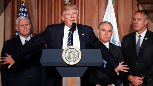President Donald Trump, accompanied by from left, Vice President Mike Pence, Environmental Protection Agency (EPA) Administrator Scott Pruitt, and Interior Secretary Ryan Zinke, speaks at EPA headquarters in Washington, Tuesday, March 28, 2017, prior to signing an Energy Independence Executive Order. Trump signed an executive order aimed at moving forward on his campaign pledge to unravel former President Barack Obama's plan to curb global warming.