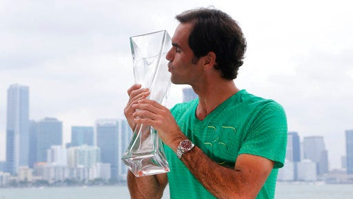Roger Federer, of Switzerland, poses for a photograph with his trophy in front of the Miami skyline after defeating Rafael Nadal in the men's singles final at the Miami Open tennis tournament, Sunday, April 2, 2017, in Miami.