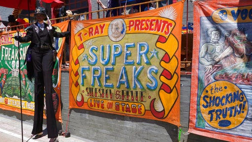 In this Sunday, April 30, 2017 photo, a stilt walker stands by a banner advertising the Venice Beach Freakshow along the strand in the Venice beach section of Los Angeles. The Venice Beach Freakshow possibly performed its last show on Sunday after announcing it is closing due to a leasing dispute. The Freakshow put on a six-hour performance on the boardwalk serving as a protest, farewell and fundraiser.