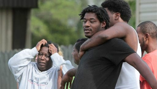Jarmal Thompson, center, of Gulfport, Miss., is held by his cousin, Jacque Chambers, after they talked to police at a trailer on Whitney Drive in Gulfport where the body of Thompson's daughter, five-year-old Janaya Thompson, was found today in a vacant mobile home, and her death is being investigated as a homicide.The child had last been seen in the parking lot outside the apartment about 8:30 p.m. Wednesday.
