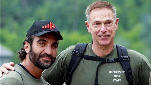 In this photo taken Aug. 6, 2014, Afghan native Fahim Fazli, left, and retired Marine Michael Moffett pose for a photo at the base of Mount Washington, N.H. before ascending the mountain via the Ammonoosuc Ravine Trail. The two are co-authors of a book about Fazli's life as an Afghan native who fled his country, became a U.S. Citizen, a Hollywood actor who played roles as a Middle eastern terrorist, and returned to Afghanistan to be a translator for U.S. Marines. The two hiked Mount Washington in hopes the Presidential Range would be a stand in for a movie for  Asia's Hindu Kush mountains.