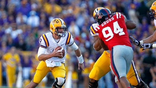 LSU quarterback Zach Mettenberger (8) scrambles pastMississippi defensive lineman Issac Gross (94) in the first half of an NCAA college football game in Baton Rouge, La., Saturday, Nov. 17, 2012. (AP Photo/Gerald Herbert)