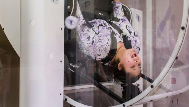 Keilani Roman spins upside down in the GyroStim machine at GyroStim of Delaware on Thursday evening.