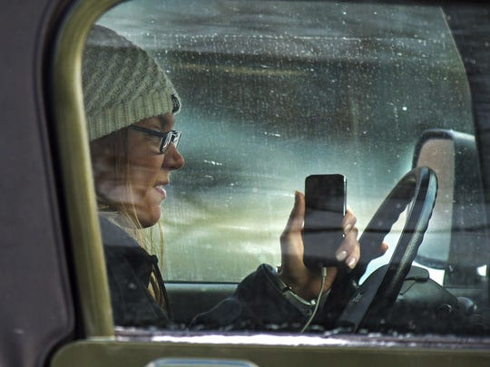 A driver uses a cell phone while stopped at a light