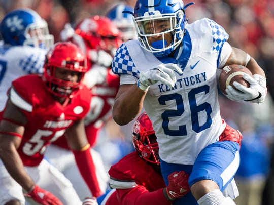 UK's Benny Snell Jr. breaks a run during the first half of UK's 41-38 victory over U of L at Papa John's Cardinal Stadium on Saturday. Nov. 26, 2016