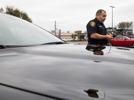 Corpus Christi police Senior Officer Gilbert Casas in the departments new stealth car gives a citation to a drive for using their cellphone on Thursday, March 8, 2018.
