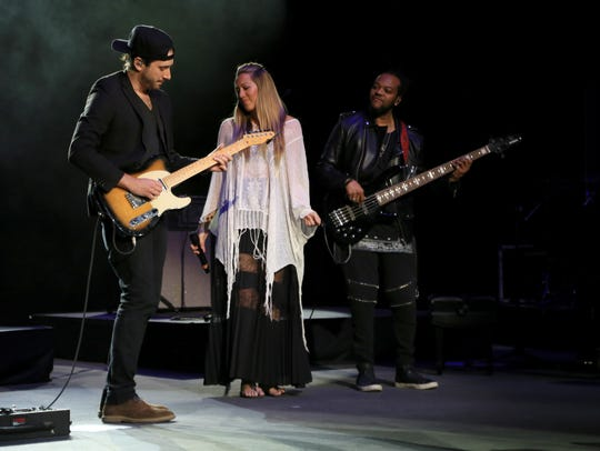 Colbie Caillat sways on the stage between two members