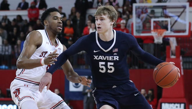 Xavier Musketeers guard J.P. Macura (55) works the ball around St. John's Red Storm guard Justin Simon (5) during the first half at Carnesecca Arena.