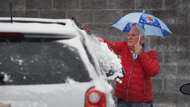 Ira Marootian of Fairfield removes snow from his car while holding a small umbrella as snow falls in Paterson on 02/07/18.