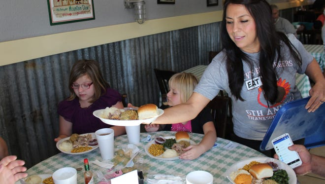 Brenda Sotelo serves a plate filled with Thanksgiving meal favorites on Thursday at Lucy's Big Burgers. Volunteers took orders and delivered meals to tables at no cost to visitors.