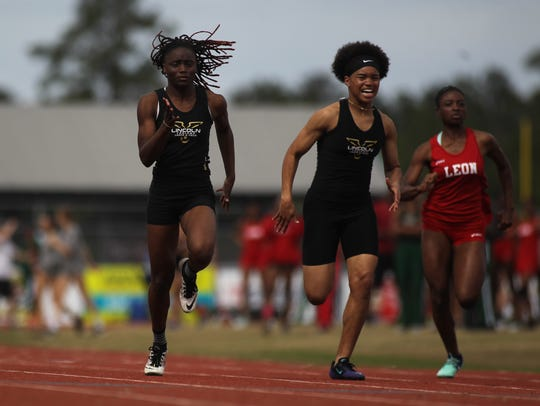 Lincoln's Jacquevia Jones (left) runs the 100-meter