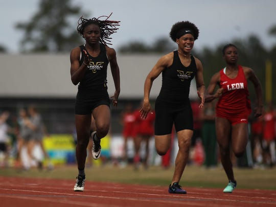 Lincoln's Jacquevia Jones (left) runs the 100-meter dash at the 2018 Chiles Track & Field Relays.