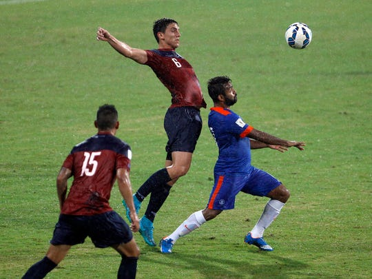 India's Cavin Peter Lobo, right, Guam's  Mason Douglas, center, and Shawn Nicklaw in action during their 2018 FIFA World Cup qualifying soccer match in Bangalore, India, Thursday, Nov. 12, 2015. India won the match 1-0.