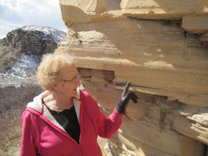 Macie Ahlgren points to historical graffiti at Bear