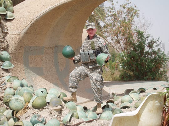 Andrew Duffy of Iowa City was a medic in Iraq. Here he encounters a pile of what he says are helmets from Iranian soldiers.